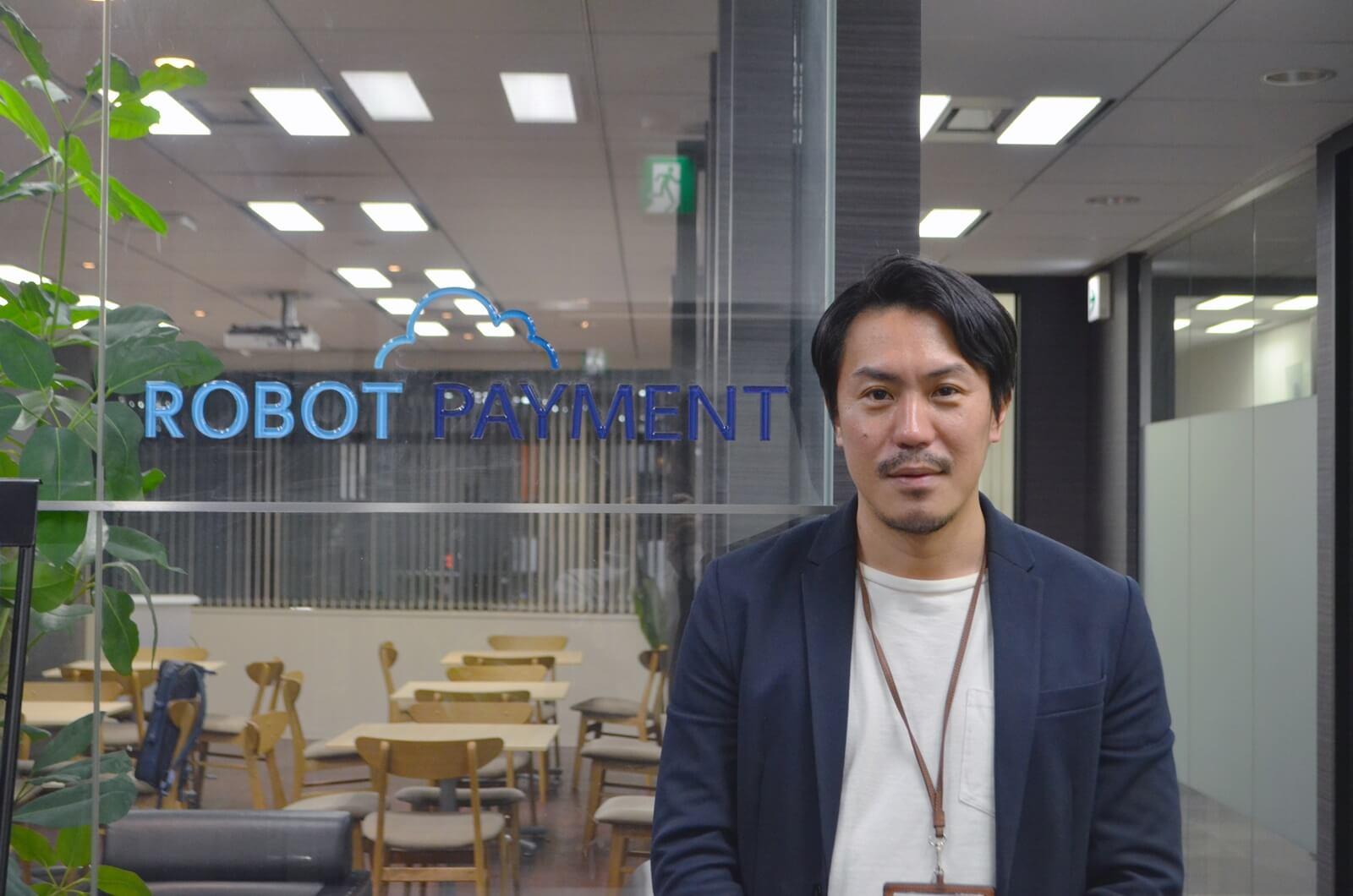 ロボットペイメントのロゴと小倉氏